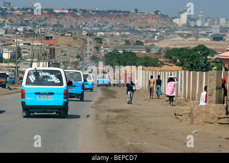 People walking along busy road in suburb of capital city Luanda, Angola, Southern Africa - Stock Photo