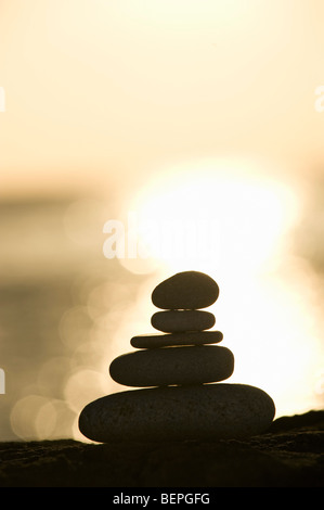 A stone stack against a setting sun - Stock Photo