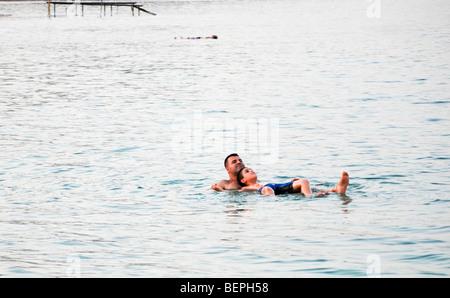 Israel, Dead Sea People float in the heavy water of the Dead Sea - Stock Photo