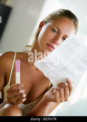 blonde woman holding pregnancy test and reading information. - Stock Photo