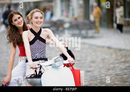 girlfriends on a motor scooter - Stock Photo