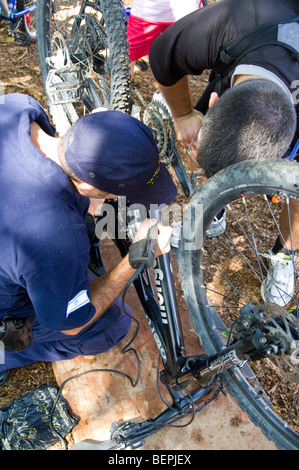 policeman marks a bicycle as a theft prevention measure by engraving a serial number onto the bike's frame - Stock Photo