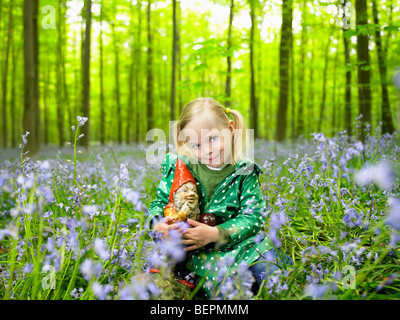 Girl with a garden gnome, in the woods - Stock Photo