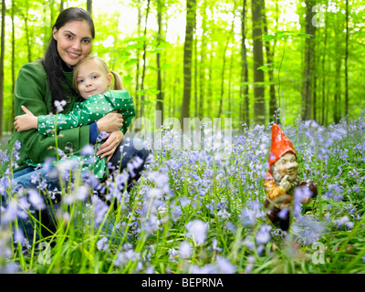 Mother and daughter next to garden gnome - Stock Photo