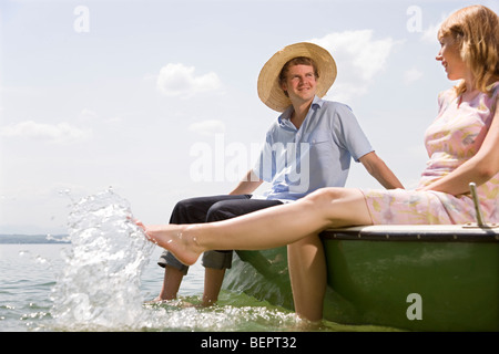 woman and man in rowing boat on lake - Stock Photo