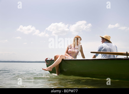 man, woman in rowing boat on lake - Stock Photo