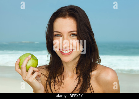 Portrait of young women eating an apple - Stock Photo