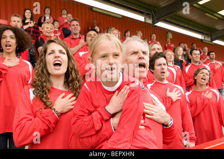 Fans singing anthem at football match - Stock Photo
