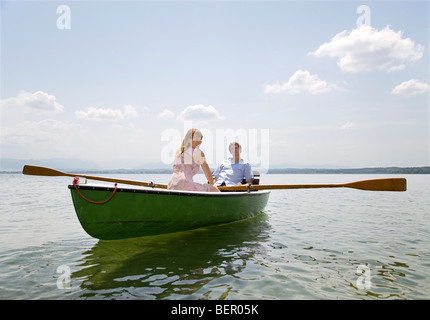 woman and man rowing boat on lake - Stock Photo