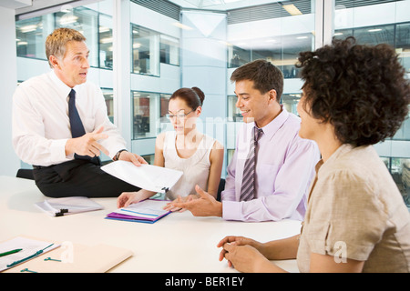 A senior male heads a business meeting - Stock Photo