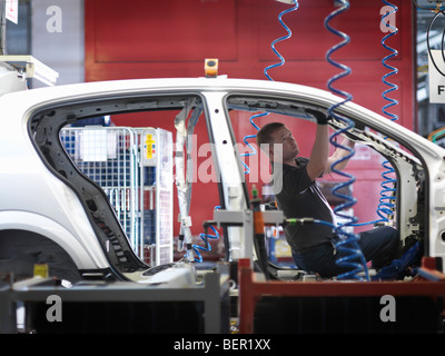 Worker Assembling Car On Production Line - Stock Photo