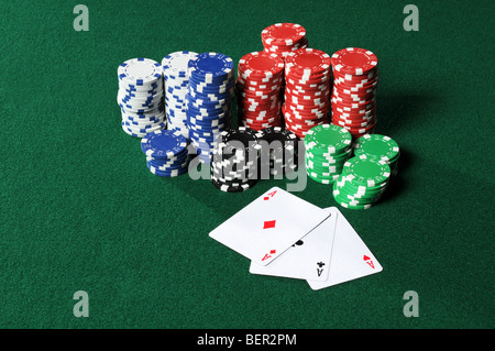 Four aces and a pile of poker chips on green table - Stock Photo