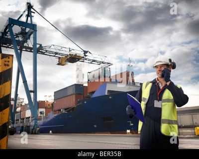 Port Worker In Front Of Loaded Ship - Stock Photo