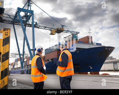 Port Workers With Ship Being Loaded - Stock Photo