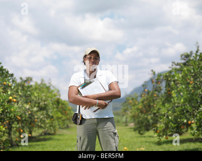 Woman With Clipboard In Orange Grove - Stock Photo