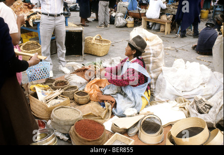 Woman sits on ground in midst of small sacks and baskets of spices. Ecuadorian Highland Marke - Stock Photo