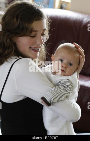 Teenage mum loves her baby - Stock Photo