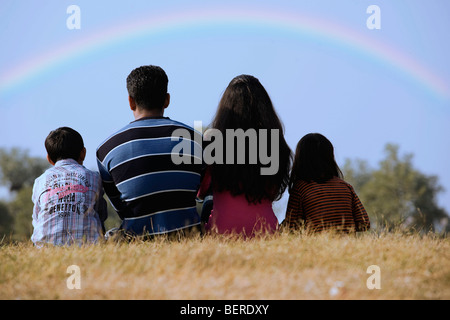 Family sitting in a park - Stock Photo