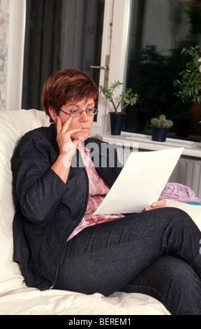 Mature woman sit on sofa at home and reading forms or confusing contract or  complicated paper  or unclear document - Stock Photo