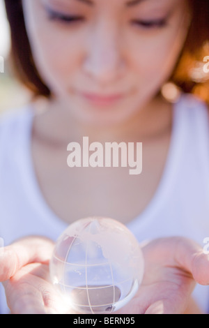 Young woman holding globe in hands, close up - Stock Photo