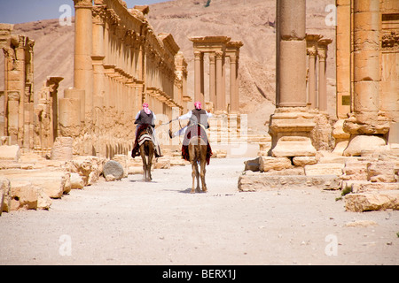 Men riding camels, roman ruins and archaeological site in Palmyra, Syria, Middle East, Asia - Stock Photo