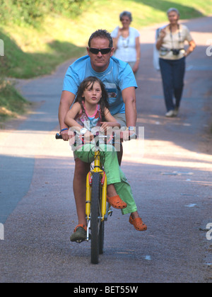 Man riding along a country road with young girl sat on the cross bar. - Stock Photo
