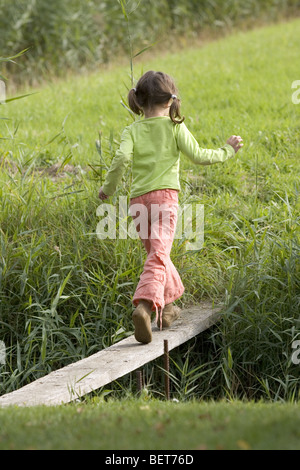 Girl walk on wooden shell rear view, stay in balance - Stock Photo