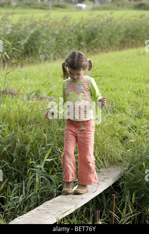 Girl balancing walk on wooden shell - Stock Photo
