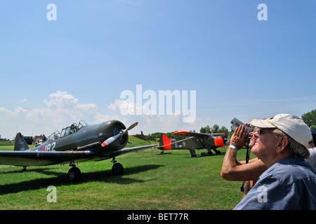 Spectators on airfield looking up at aerobatics during airshow in Koksijde, Belgium - Stock Photo