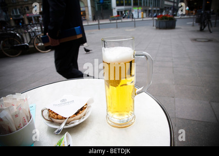 A glass of German beer and peanuts on a table on pavement cafe in Frankfurt Germany. - Stock Photo