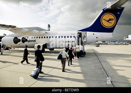 Passengers board a Lufthansa Regional Airline plane at Frankfurt Airport Germany bound for City Airport London. - Stock Photo
