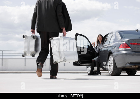 man carrying cases woman waiting in car - Stock Photo