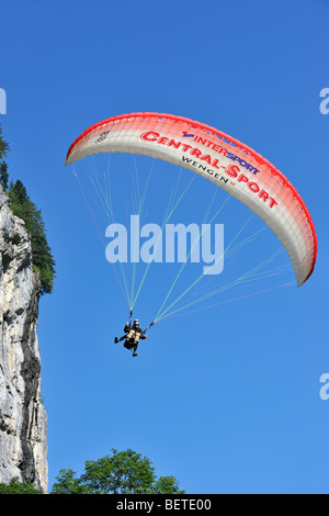 Tandem paraglider with pilot and passenger flying along rock face in the Swiss Alps, Switzerland - Stock Photo