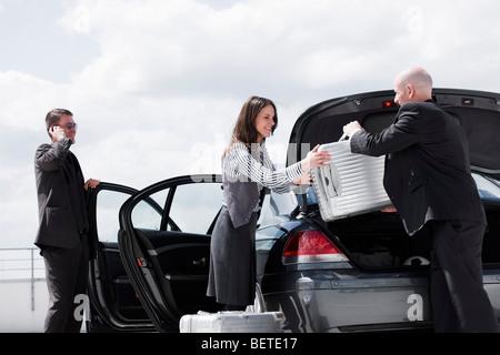 man handing suitcase to woman - Stock Photo