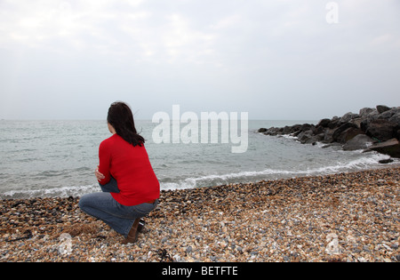 Back view of slim dark haired woman looking away into the distance. - Stock Photo