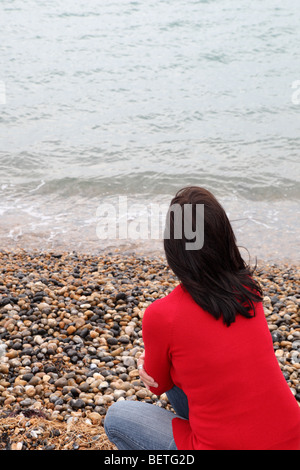 Back view of slim dark haired woman looking away into the distance - Stock Photo