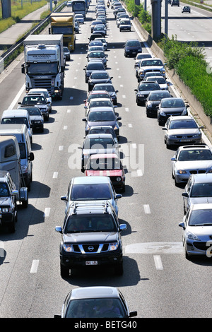 Cars and trucks queueing in highway lanes during traffic jam on motorway during summer holidays, Belgium - Stock Photo