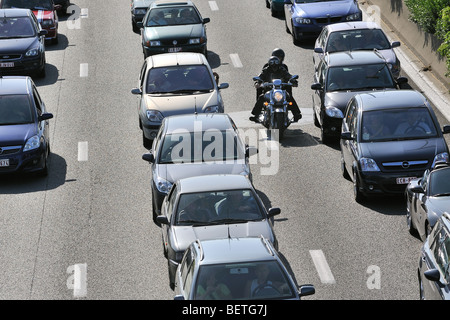 Motorcyclist riding between cars in traffic jam on motorway during the summer holidays, Belgium - Stock Photo