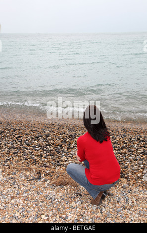 Back view of slim dark haired woman looking away into the distance contemplating the future - Stock Photo