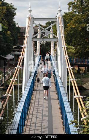 Pedestrians crossing the footbridge bridge over the River Thames at Teddington Lock, Teddington Middx, UK. - Stock Photo
