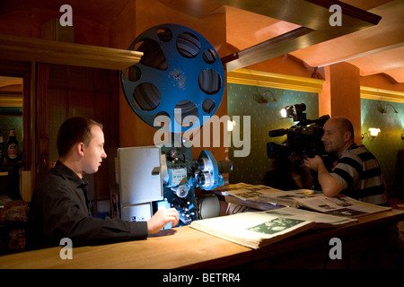 TV camera filming cinema projectionist - Stock Photo
