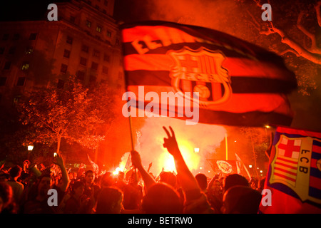 Victory celebration of the football fan crowd waving with a flag in Barcelona. - Stock Photo