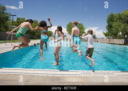 Kids Public Swimming Pool five people jumping into swimming pool stock photo, royalty free