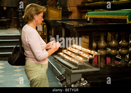 Woman (probably with Polish nationality) lights a vigil candle in the church of St Marys Basilica. Krakow. Poland. - Stock Photo