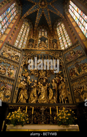 Altarpiece by Veit Stoss in the nave of St Marys Basilica, in front of the East wall apse stained glass windows. - Stock Photo