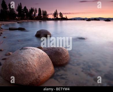 Sunset on eroded granite boulders at Sand Harbor, Lake Tahoe, Nevada - Stock Photo