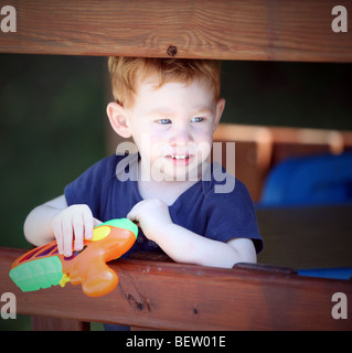 Boy in wooden play fort with toy gun - Stock Photo