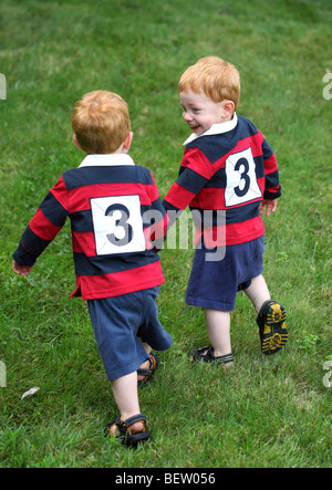 Twin baby boys holding hands outside - Stock Photo