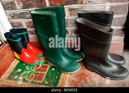 Three pairs of wellingtons on the doorstep - mum 's dad 's and child's - with seasonal doormat as Christmas is near. - Stock Photo