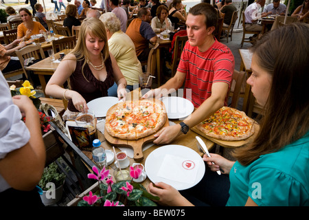 Young English tourists eat a pizza meal on outdoor restaurant tables in The Main Market Square / Markt Square. Krakow. - Stock Photo